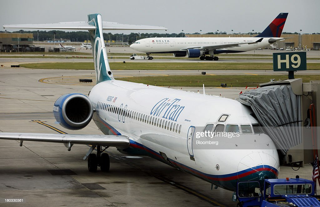 A Delta Air Lines Airbus A330-223 plane taxis down the runway as an AirTran Holdings Inc. Boeing 717-231 jet sit on the tarmac at Minneapolis-St. Paul International Airport (MSP) in Minneapolis, Minnesota, U.S., on Sunday, Sept. 8, 2013. Yields on benchmark securities climbed to almost two-year highs as consumers spent more on travel and tourism while manufacturing expanded modestly from early July through late August, according to the Federal Reserves Beige Book. Photographer: Patrick T. Fallon/Bloomberg via Getty Images