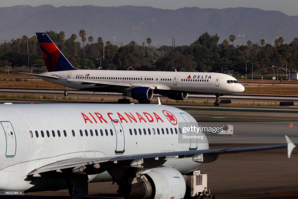 A Delta Air Lines Inc. Boeing Co. 757-212 planes taxis down the runway past an Air Canada jet on the tarmac at Los Angeles International Airport (LAX) in Los Angeles, California, U.S., on Friday, Sept. 6, 2013. Yields on benchmark securities climbed to almost two-year highs as consumers spent more on travel and tourism while manufacturing expanded modestly from early July through late August, according to the Federal Reserves Beige Book. Photographer: Patrick T. Fallon/Bloomberg via Getty Images