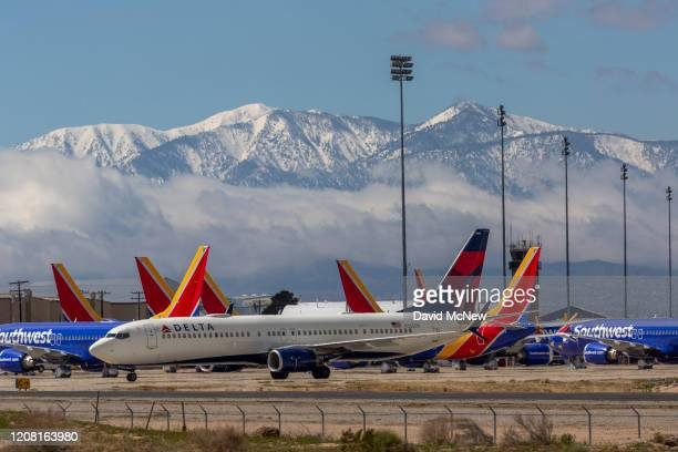 Delta Air Lines jet taxis passed Southwest Airlines jets to be parked with a growing number of jets at Southern California Logistics Airport on March...