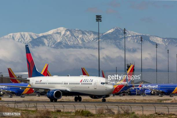 Delta Air Lines jet taxis passes Southwest Airlines jets to be parked with a growing number of jets at Southern California Logistics Airport on March...