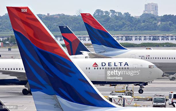 Delta Air Lines plane taxis toward a gate between other Delta planes at John F. Kennedy International Airport in New York, U.S., on Monday, July 20,...