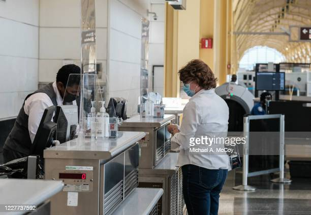 Delta Airline employee checks in a passenger at the Ronald Reagan National Airport on July 22, 2020 in Arlington, Virginia. During the COVID-19...