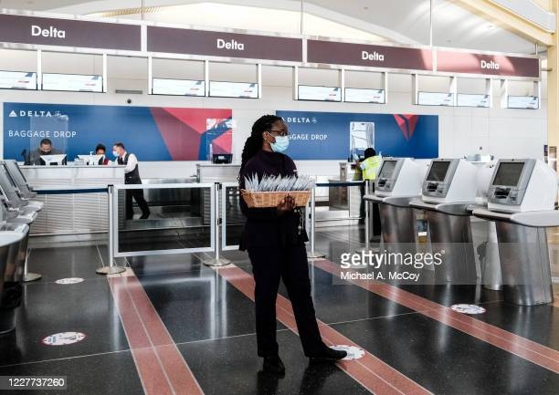 Delta Airline employee hands out face masks to passengers during check in at the Ronald Reagan National Airport on July 22, 2020 in Arlington,...