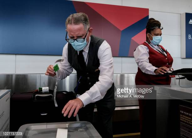 Delta Airline employees check in luggage at the Ronald Reagan National Airport on July 22, 2020 in Arlington, Virginia. During the COVID-19 pandemic,...