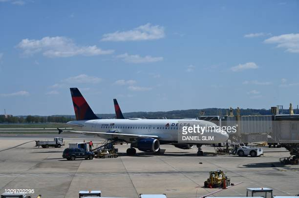 Delta Airlines airplane is seen at gate at Washington National Airport on April 11, 2020 in Arlington, Virginia. - Many flights are canceled due to...