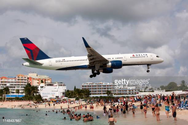 Delta Airlines Boeing 757 seen landing at airport Princess Juliana just over Maho beach.