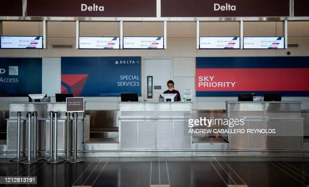 Delta airlines employee waits for passengers at an empty check-in counter in Ronald Reagan Washington National Airport in Arlington, Virginia, on May...