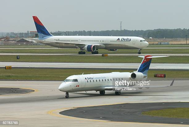 Delta Airlines planes roll to the terminal at Hartsfield Jackson Airport May 10 2005 in Atlanta Georgia Delta has announced that it expects a...