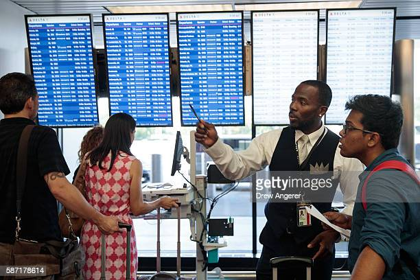 Delta employee helps travelers near the Delta checkin counter at LaGuardia Airport August 8 2016 in the Queens borough of New York City Delta flights...