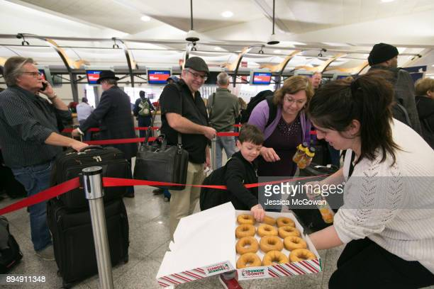 Delta employee passes out doughnuts and juice to Braxton Bryan and his grandparents Michael and Stacey Cryer of Pineville LA as they wait in line to...