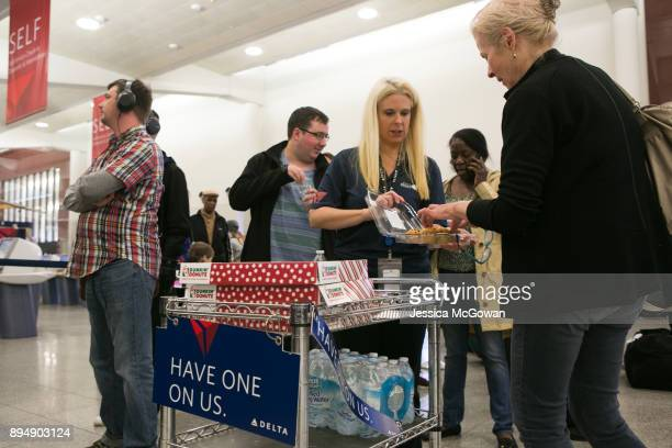Delta employee Shannon Nardone passes out free muffins doughnuts and water to passengers at HartsfieldJackson Atlanta International Airport on...