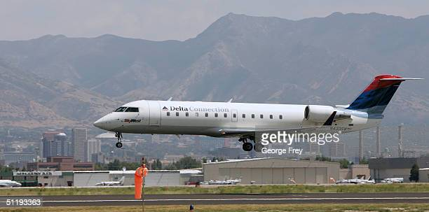 Delta flight lands at the Salt Lake City International Airport with downtown Salt Lake City in the background August 19 2004 in Salt Lake City Utah...