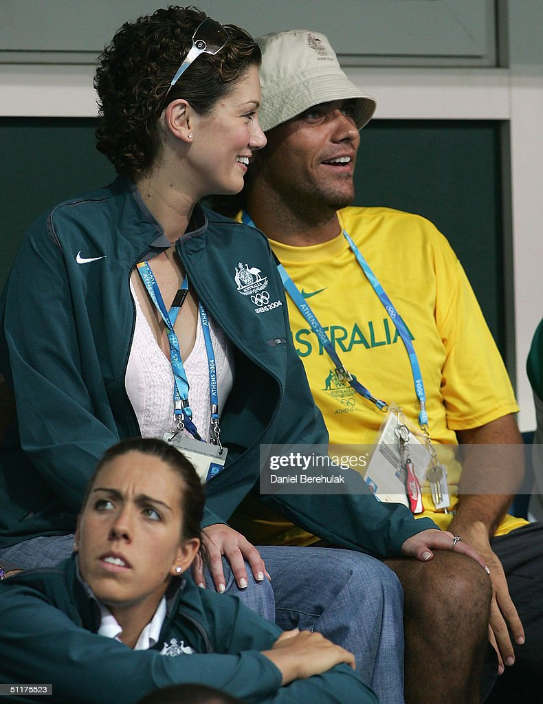 Delta Goodrem and Mark Phillippoussis look on during the women's swimming 100 metre butterfly final on August 15, 2004 during the Athens 2004 Summer Olympic Games at the Main Pool of the Olympic Sports Complex Aquatic Centre in Athens, Greece.