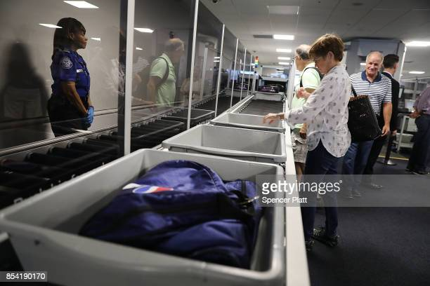Delta passengers have their luggage screened at LaGuardia Airport on September 26, 2017 in New York City. Passengers traveling through Terminal C...