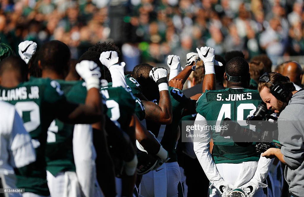 Delton Williams #22 of the Michigan State Spartans and other teammates held up their first during the playing of the National Anthem prior to the start of the game against the Brigham Young Cougars at Spartan Stadium on October 8, 2016 in East Lansing, Michigan. Brigham Young defeated Michigan State 31-14.