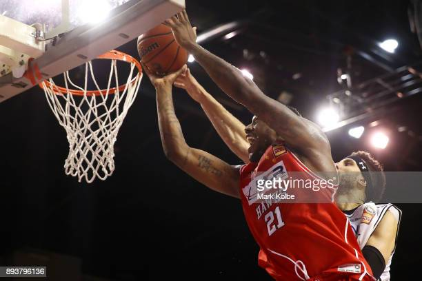 Delvon Johnson of the Hawks drives to the basket under pressure from Josh Boone of Melbourne United during the round 10 NBL match between the...