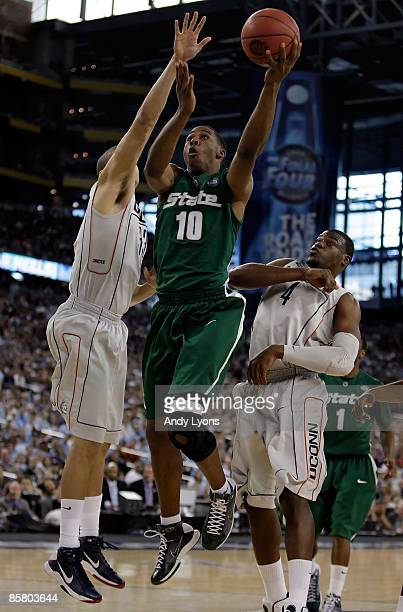 Delvon Roe of the Michigan State Spartans goes up for a shot against Gavin Edwards and Jeff Adrien of the Connecticut Huskies in the first half...
