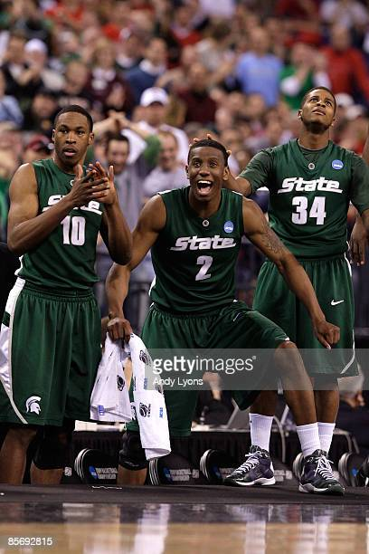 Delvon Roe, Raymar Morgan and Korie Lucious of the Michigan State Spartans support their team from the bench late in their 64-52 win against the...