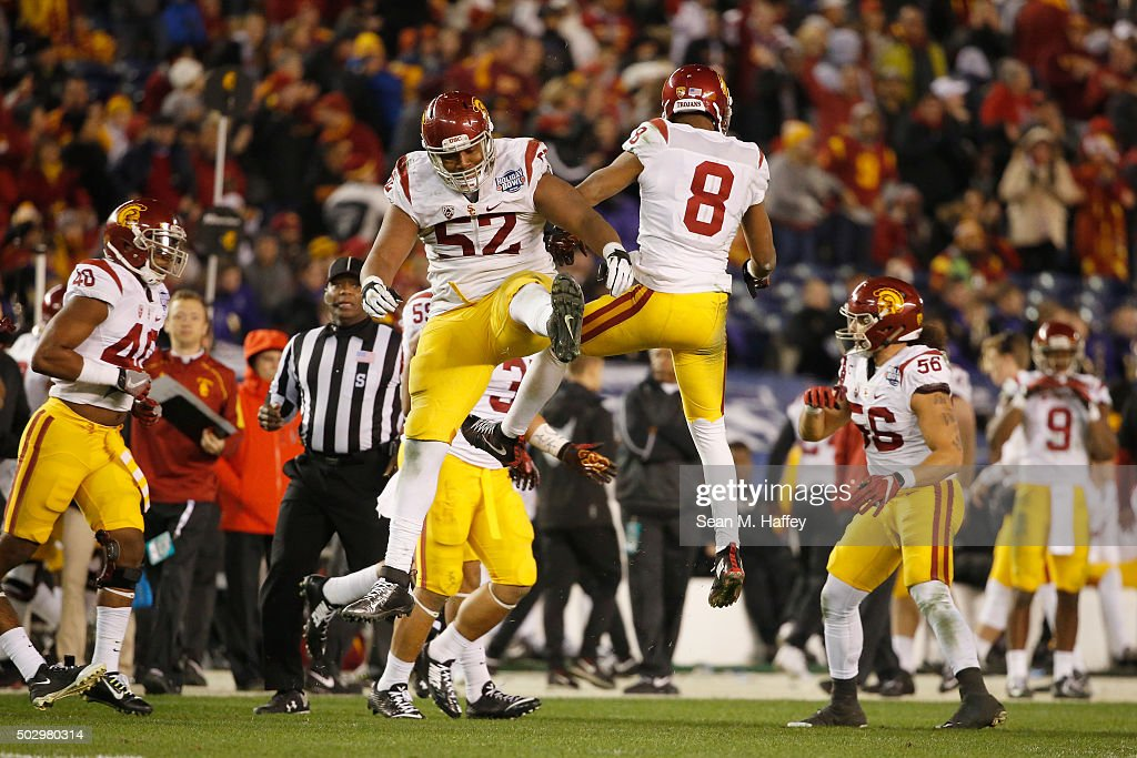 Delvon Simmons #52 of the USC Trojans reacts with Ricky Town #8 of the USC Trojans during the second half of a game against the Wisconsin Badgers during the National University Holiday Bowl at Qualcomm Stadium on December 30, 2015 in San Diego, California.
