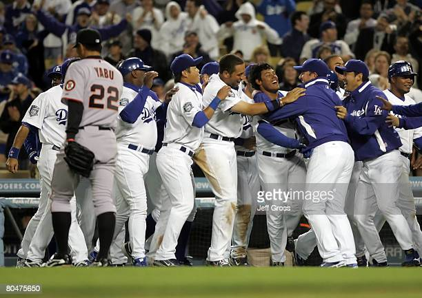 Delwyn Young of the Los Angeles Dodgers is congratulated by his teammates after hitting the game winning RBI in the ninth inning as Keiichi Yabu of...