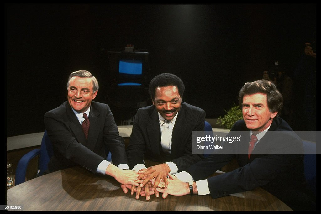 Dem. pres. rivals Gary Hart, Jesse Jackson & Walter Mondale piling linked hands, all smiles, in (rare) show of Dem. solidarity, during debate.