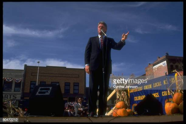 Dem presidential cand Bill Clinton on pumpkin decorated podium w carpenters union local banner addressing rally on campaign trail
