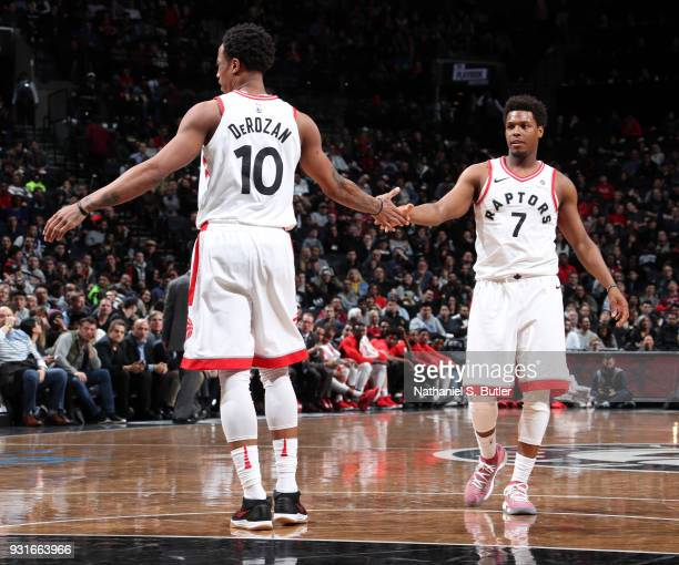 DeMar DeRozan and Kyle Lowry of the Toronto Raptors high five during the game against the Brooklyn Nets on March 13 2018 at Barclays Center in...