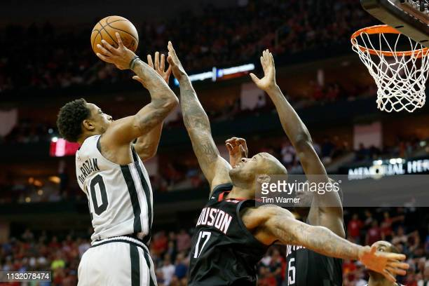 DeMar DeRozan of the San Antonio Spurs goes up for a shot defended by PJ Tucker of the Houston Rockets and Clint Capela in the fourth quarter at...