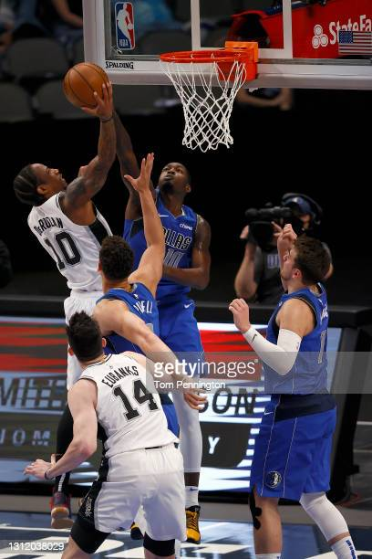 DeMar DeRozan of the San Antonio Spurs shoots the ball against Dwight Powell of the Dallas Mavericks and Dorian Finney-Smith of the Dallas Mavericks...