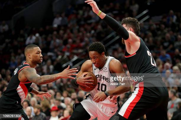 DeMar DeRozan of the San Antonio Spurs works against Damian Lillard and Jusuf Nurkic of the Portland Trail Blazers in the first quarter during their...