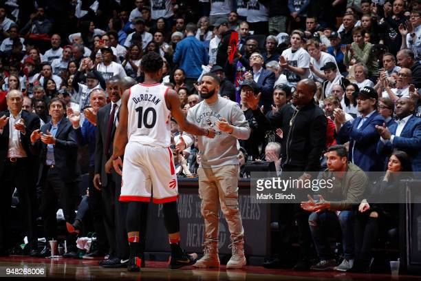 DeMar DeRozan of the Toronto Raptors and Drake react to a play during the game against the Washington Wizards in Game Two of Round One of the 2018...