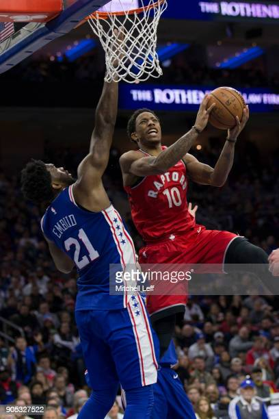 DeMar DeRozan of the Toronto Raptors attempts a shot against Joel Embiid of the Philadelphia 76ers in the fourth quarter at the Wells Fargo Center on...