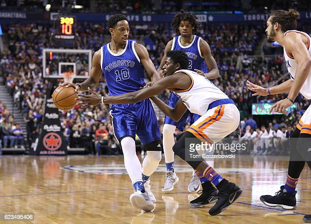 DeMar DeRozan of the Toronto Raptors dribbles as Justin Holiday of the New York Knicks defends during NBA game action at Air Canada Centre on...