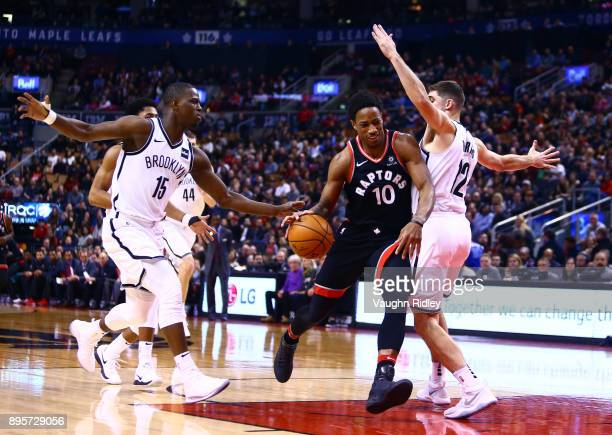 DeMar DeRozan of the Toronto Raptors dribbles the ball as Isaiah Whitehead and Joe Harris of the Brooklyn Nets defend during the first half of an NBA...