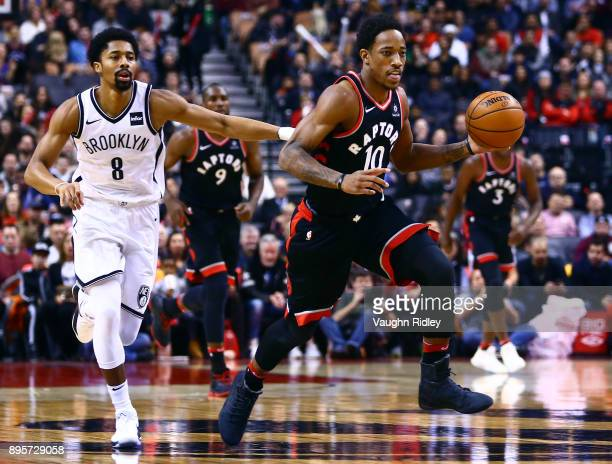 DeMar DeRozan of the Toronto Raptors dribbles the ball as Spencer Dinwiddie of the Brooklyn Nets chases during the first half of an NBA game at Air...