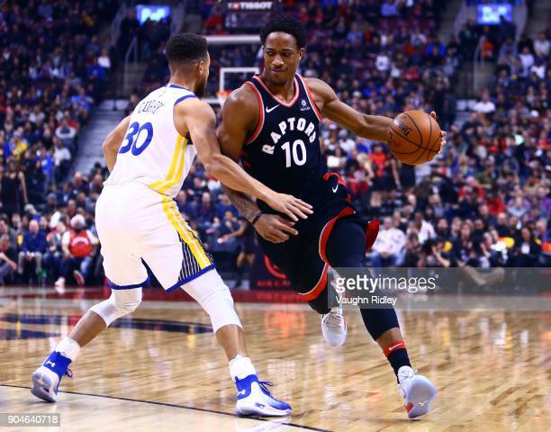 DeMar DeRozan of the Toronto Raptors dribbles the ball as Stephen Curry of the Golden State Warriors defends during the first half of an NBA game at...