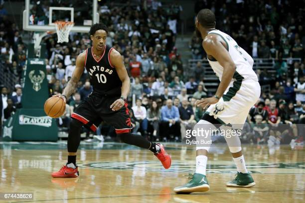 DeMar DeRozan of the Toronto Raptors dribbles the ball while being guarded by Greg Monroe of the Milwaukee Bucks in the third quarter in Game Six of...