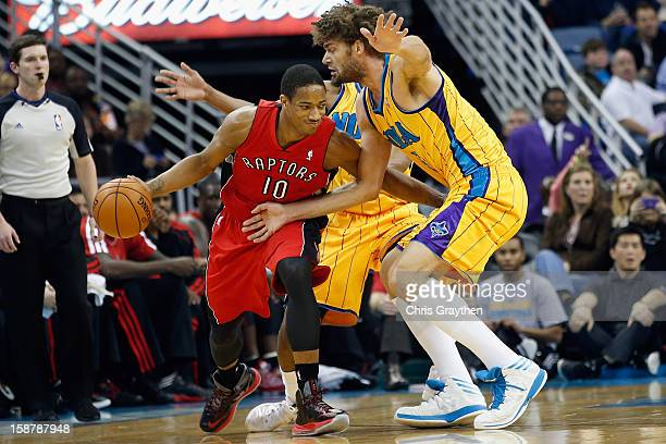 DeMar DeRozan of the Toronto Raptors drives the ball around Robin Lopez of the New Orleans Hornets at New Orleans Arena on December 28 2012 in New...