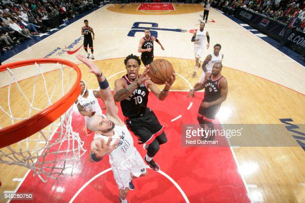 DeMar DeRozan of the Toronto Raptors goes to the basket over Marcin Gortat of the Washington Wizards in Game Three of Round One of the 2018 NBA...