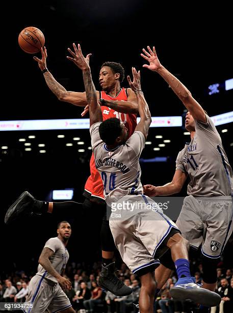 DeMar DeRozan of the Toronto Raptors passes the ball as Rondae HollisJefferson and Brook Lopez of the Brooklyn Nets defend at the Barclays Center on...