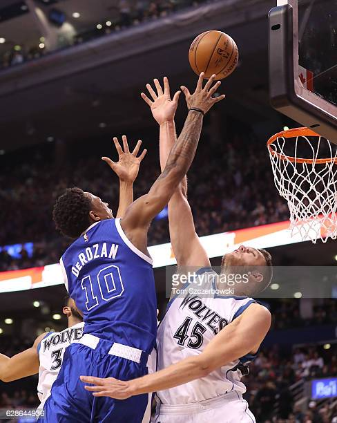 DeMar DeRozan of the Toronto Raptors scores a basket over Cole Aldrich of the Minnesota Timberwolves during NBA game action at Air Canada Centre on...