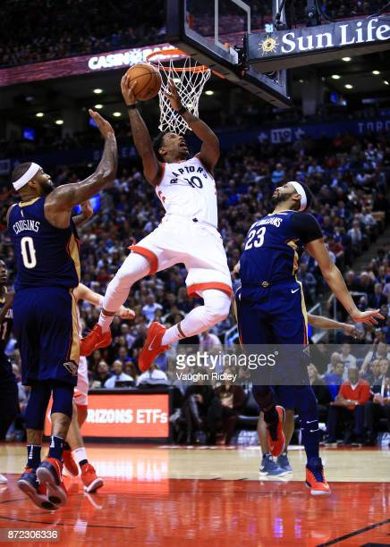 DeMar DeRozan of the Toronto Raptors shoots the ball as DeMarcus Cousins and Anthony Davis of the New Orleans Pelicans defends during the second half...