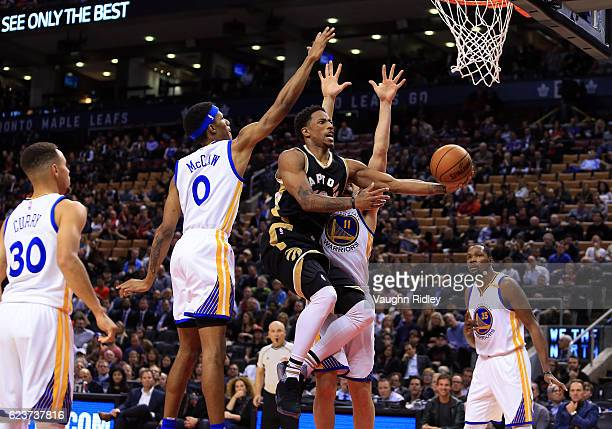 DeMar DeRozan of the Toronto Raptors shoots the ball as Patrick McCaw and Klay Thompson of the Golden State Warriors defend during the second half of...