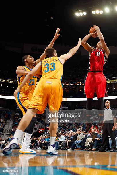 DeMar DeRozan of the Toronto Raptors shoots the ball over Ryan Anderson of the New Orleans Hornets s at New Orleans Arena on December 28 2012 in New...