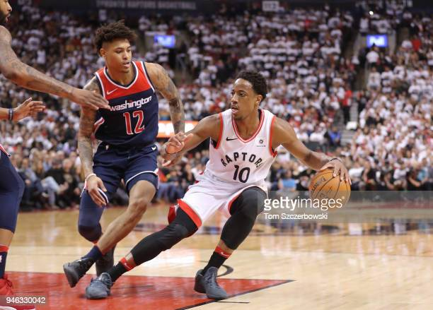 DeMar DeRozan of the Toronto Raptors stops as he dribbles as he is guarded by Kelly Oubre Jr #12 of the Washington Wizards in the third quarter...