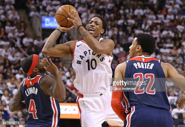DeMar DeRozan of the Toronto Raptors tries to get a shot off over Ty Lawson of the Washington Wizards in Game Two of the Eastern Conference First...