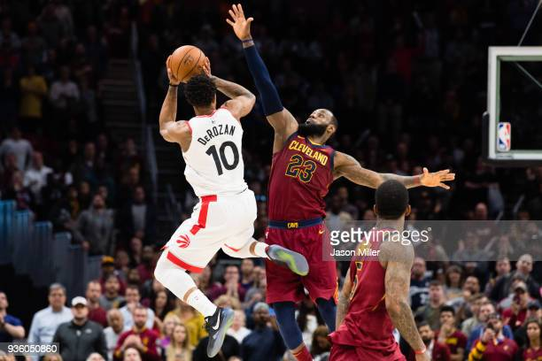 DeMar DeRozan of the Toronto Raptors tries to take a last second shot over LeBron James of the Cleveland Cavaliers during the second half at Quicken...