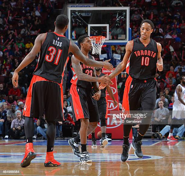 DeMar DeRozan Terrence Ross and Louis Williams of the Toronto Raptors give each other five against the Philadelphia 76ers at Wells Fargo Center on...