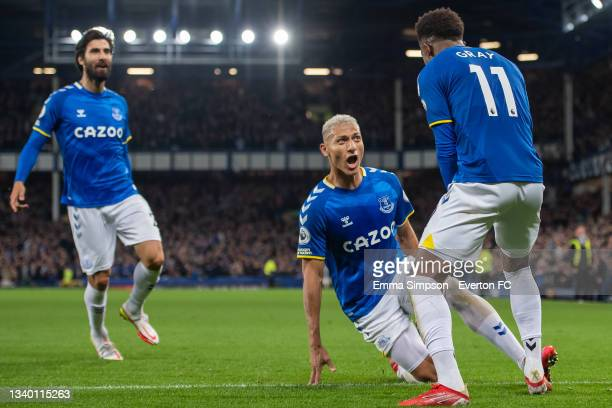 Demarai Gray of Everton celebrates scoring his team's third goal with team mates Richarlison and Andre Gomes during the Premier League match between...