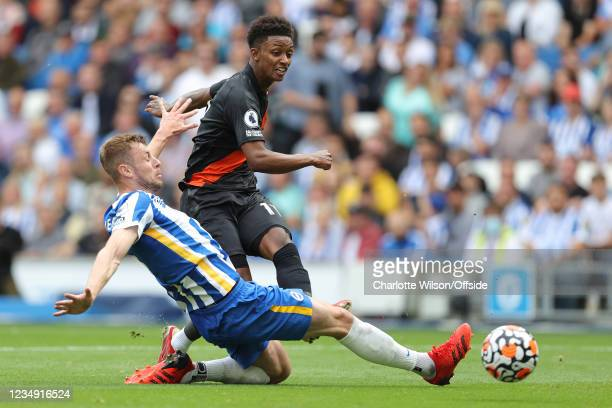 Demarai Gray of Everton scores the opening goal despite the defensive efforts of Adam Webster of Brighton & Hove Albion during the Premier League...